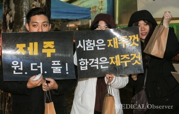 Jeju National University medical students cheer for senior candidates with hand-made pickets.